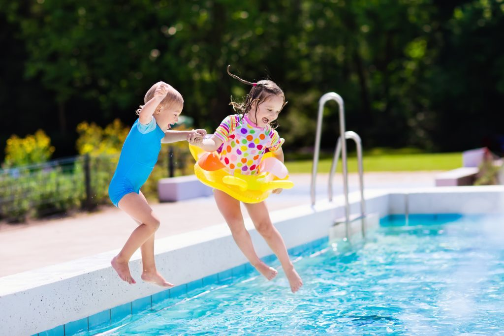 boy and girl mid air, jumping into a pool
