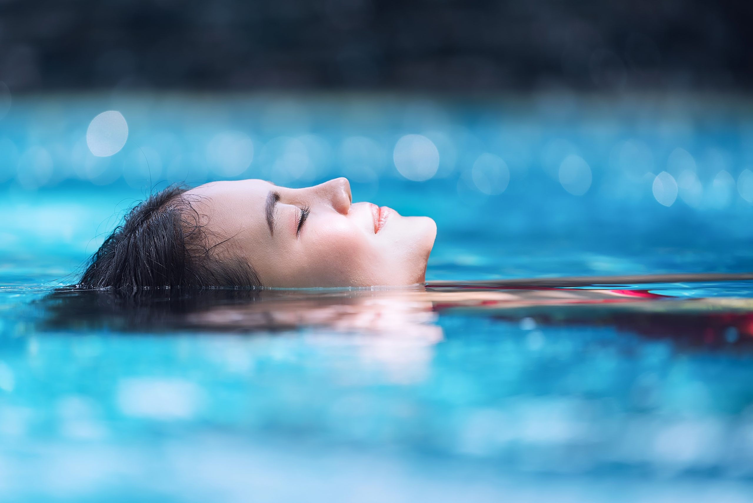 Midshot of young woman, eyes closed, relaxing in pool