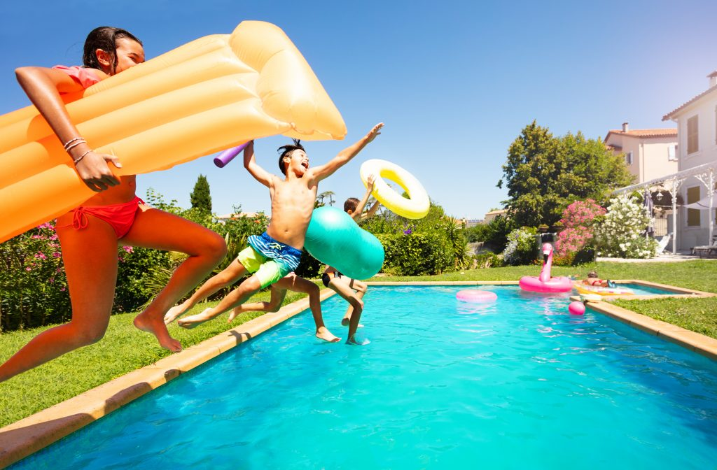 Funny teens with swim tools jumping into the pool