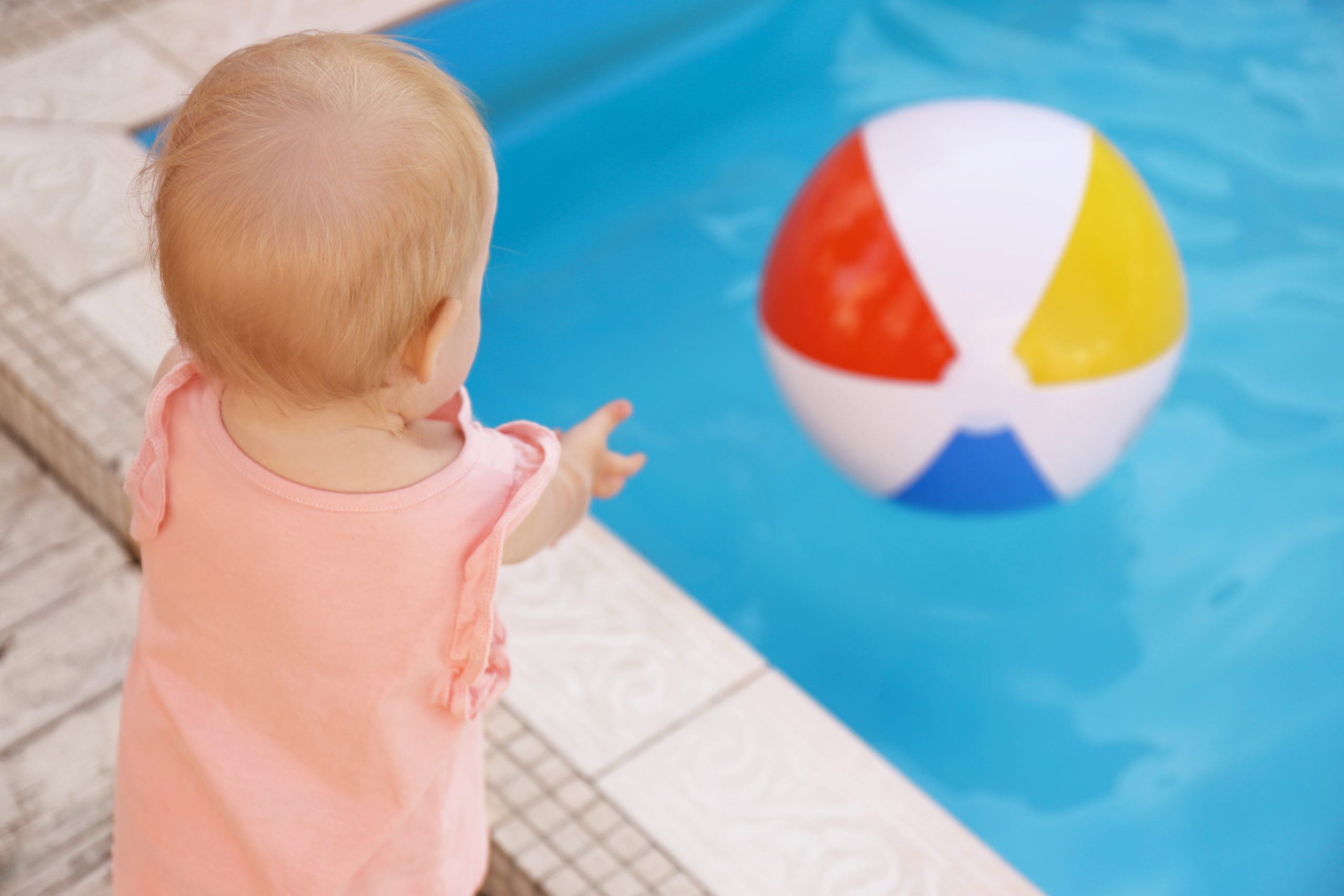 Baby throwing a ball into a pool