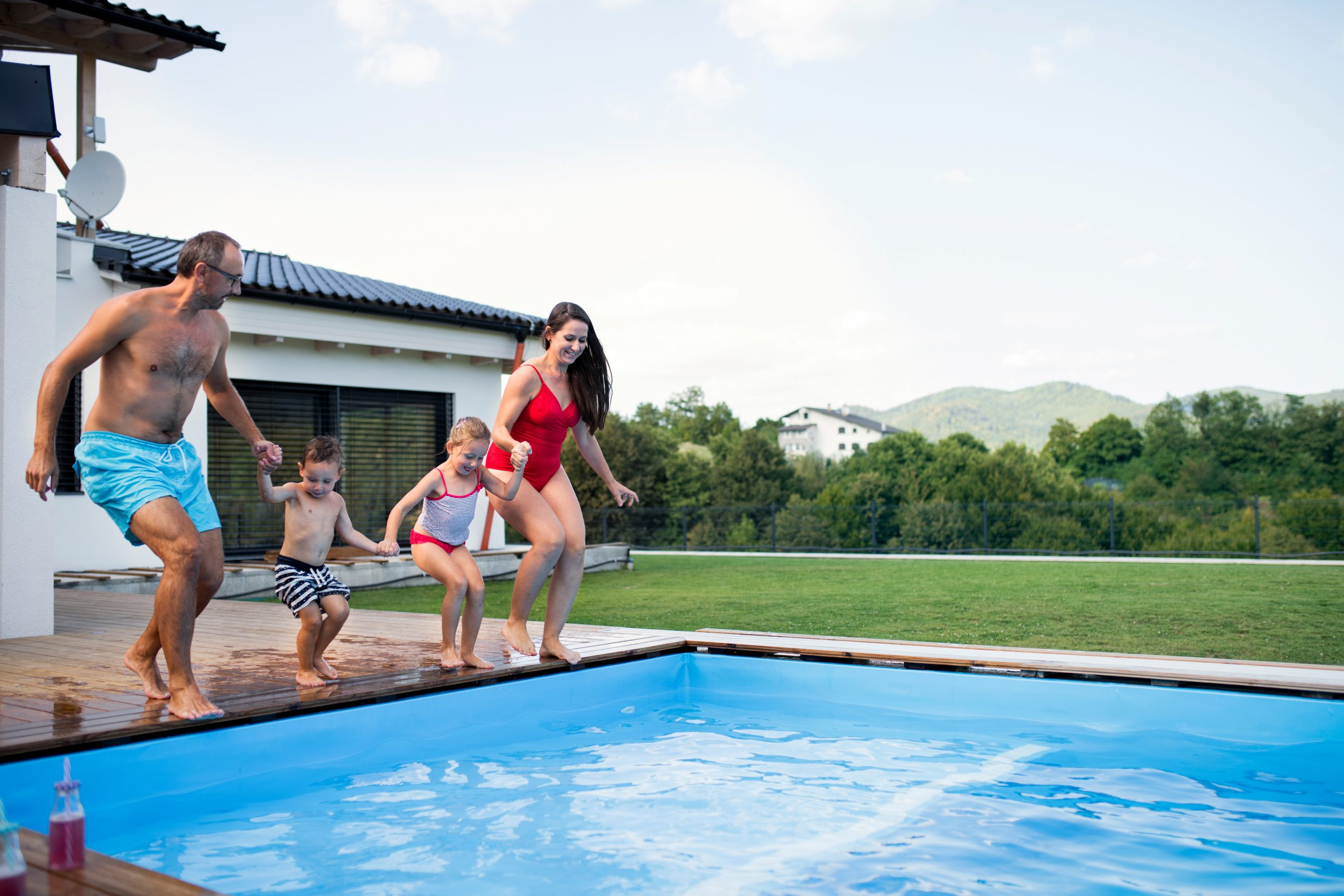 family of 4, holding hands and jumping into a backyard pool