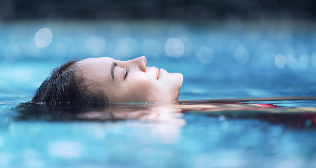 Woman lying in water with eyes closed, relaxing