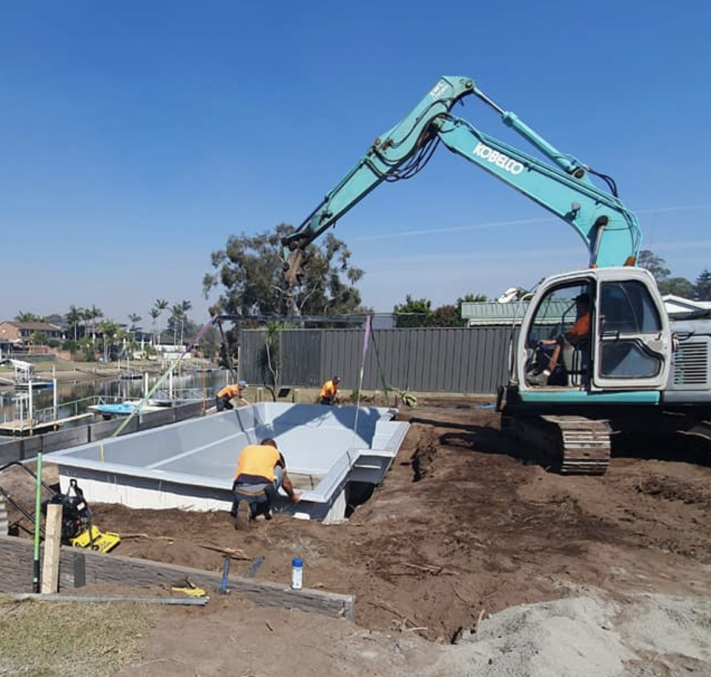 Putting in a pool using excavation equipment