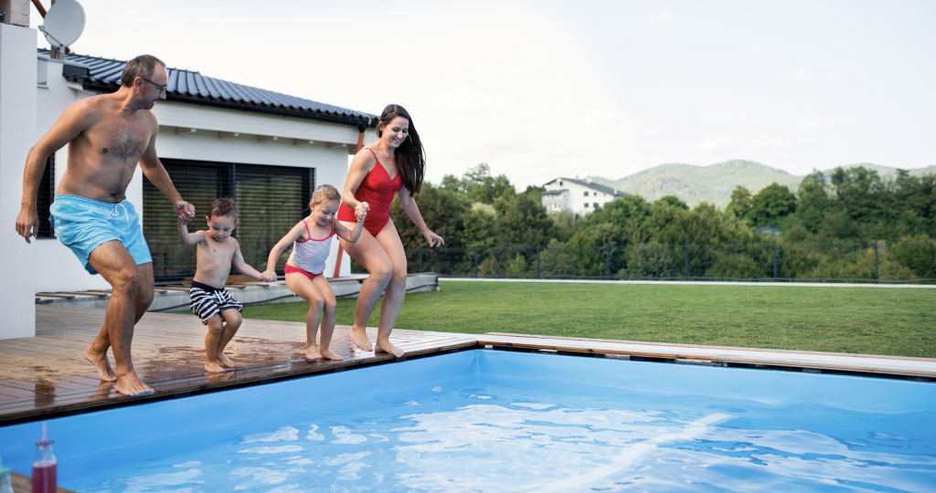Family of four holding hands while jumping into a pool