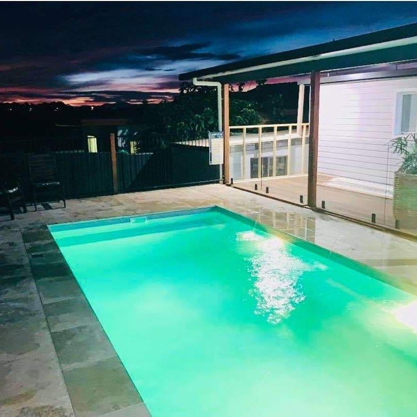 Small Backyard pool lit up at night